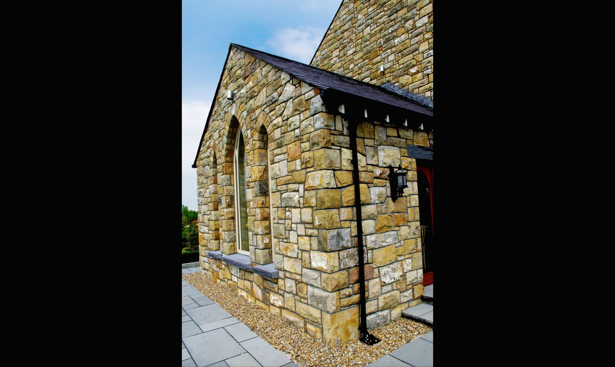 Reclaimed Leitrim sandstone. Gothic window arches. Rock faced Kilkenny limestone cills. Limestone path & steps