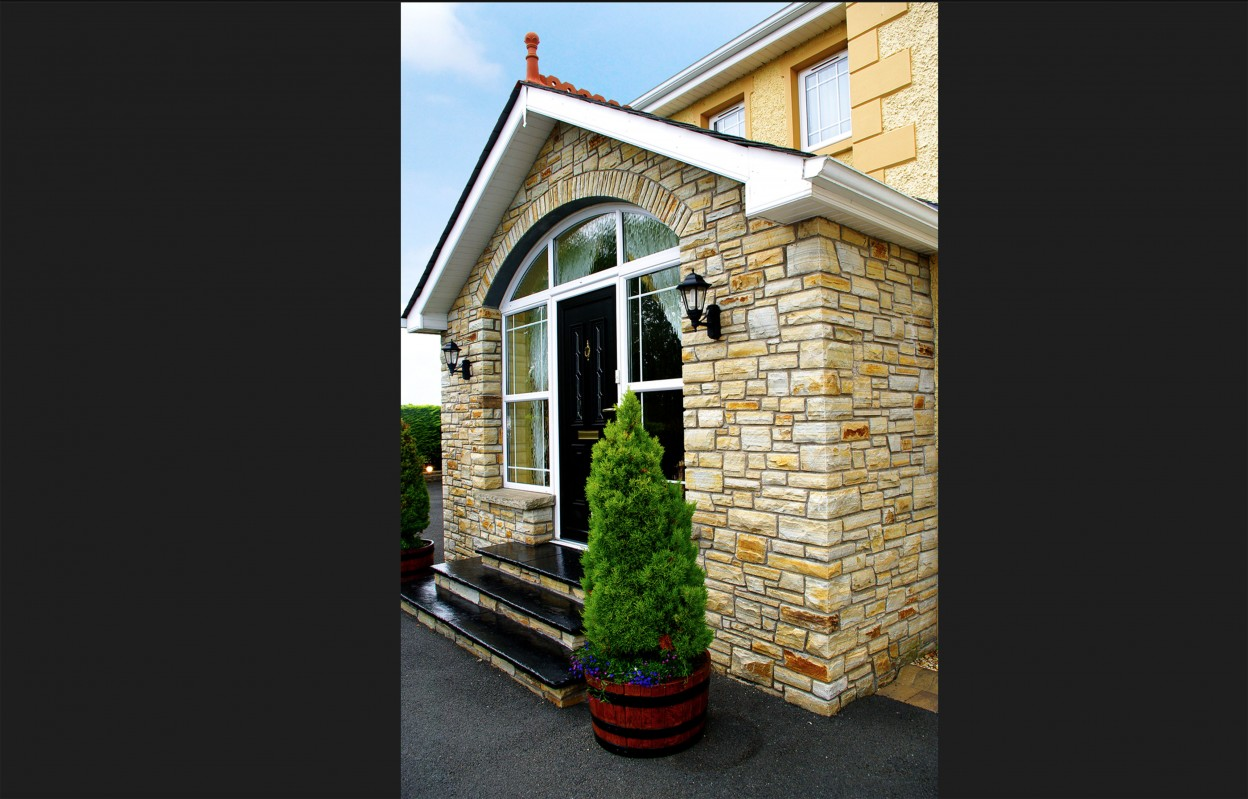 Brown Quartzite Stone Porch with arch detail built on keystone lintel