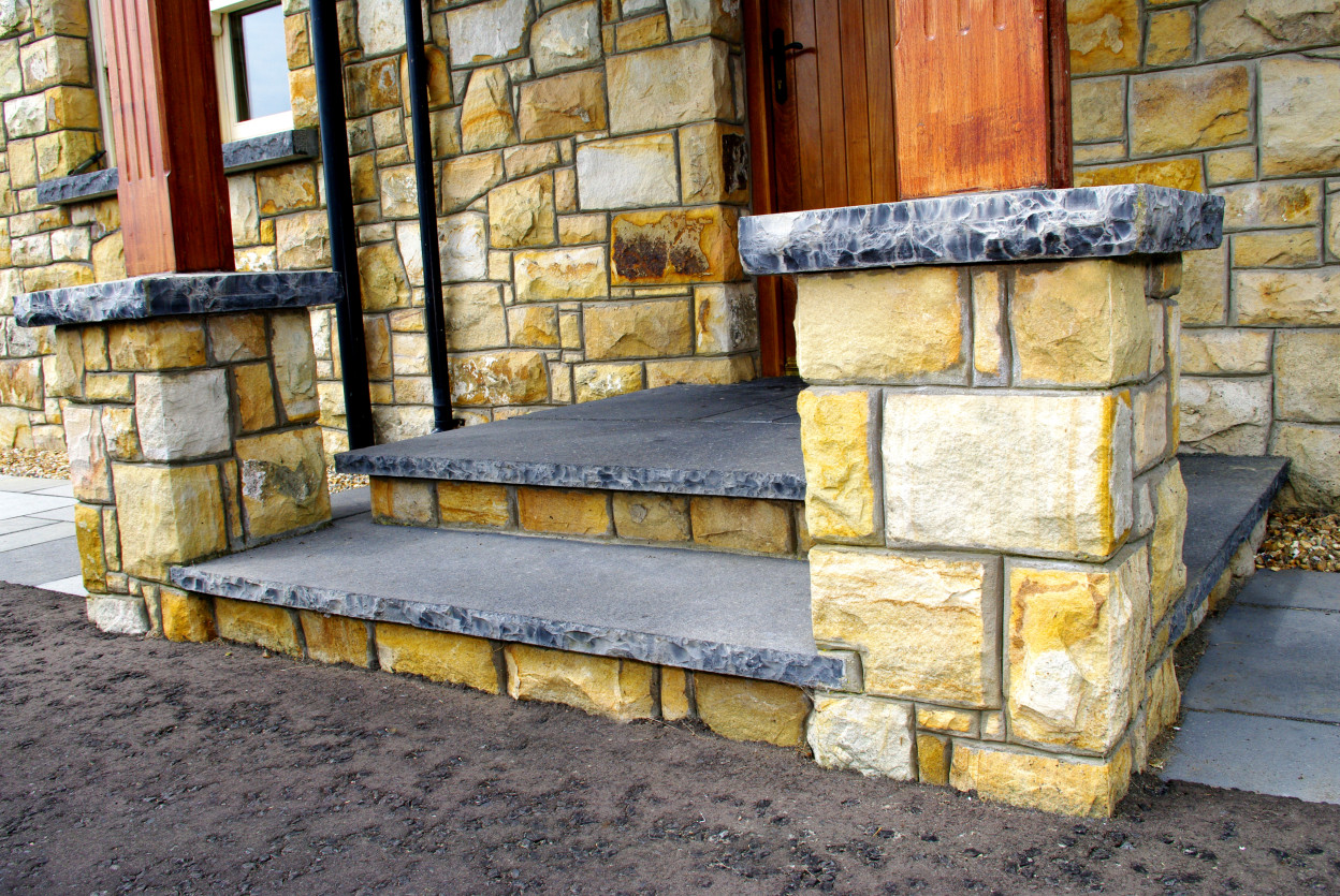 Rock faced Limestone Steps with Stone risers. Rock faced limestone coping for wooden portico roof.