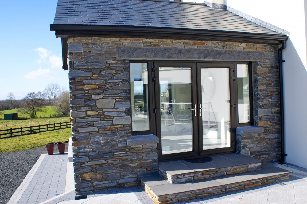 Donegal slate with rock faced limestone window cills and lintels. Steps formed using Donegal slate as risers and 22mm calibrated limestone paving for treads