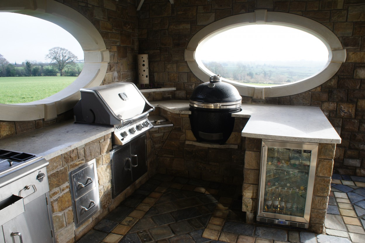 Outdoor kitchen with BBQ and stainless steel built in fridge. Donegal sandstone oval window surround. Sandstone lamp