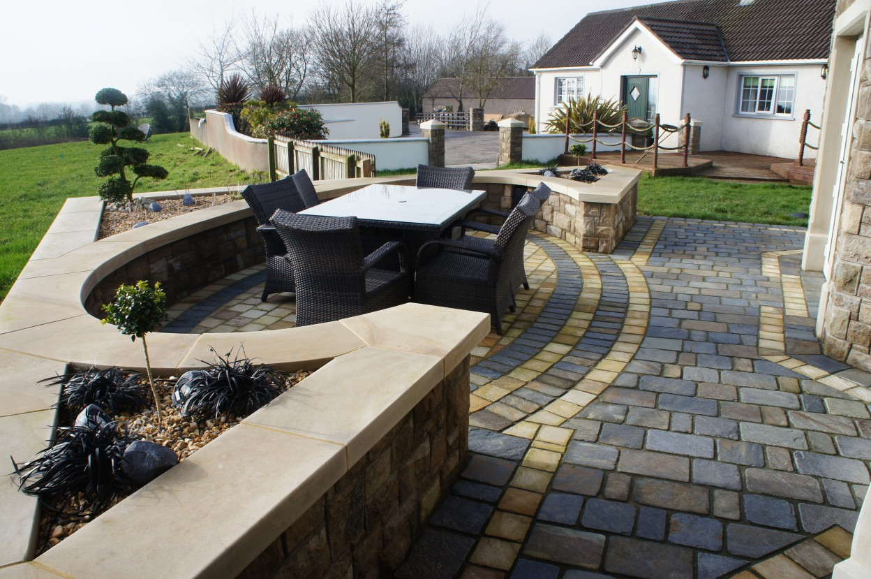 Olde English slate cobbles with 150x150 sandstone cobble border. Donegal sandstone wall copings for additional seating