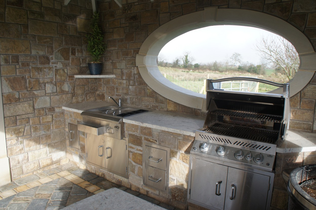 Outdoor kitchen with sink & BBQ. Granite worktop supplied by Elite Granite. Donegal sandstone oval window surround