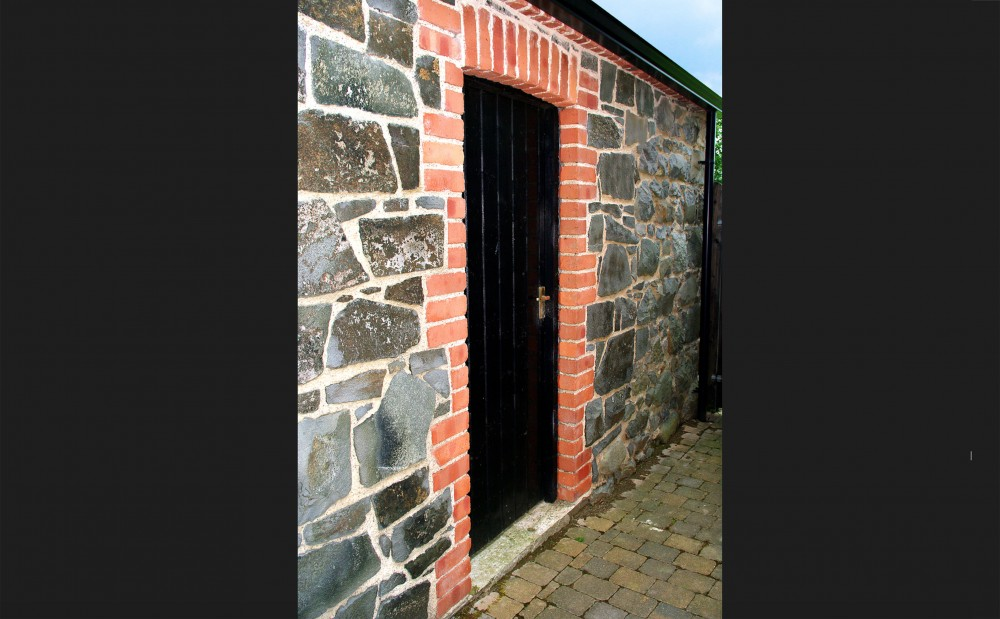 Basalt stone with red brick quoins and soldiers to door