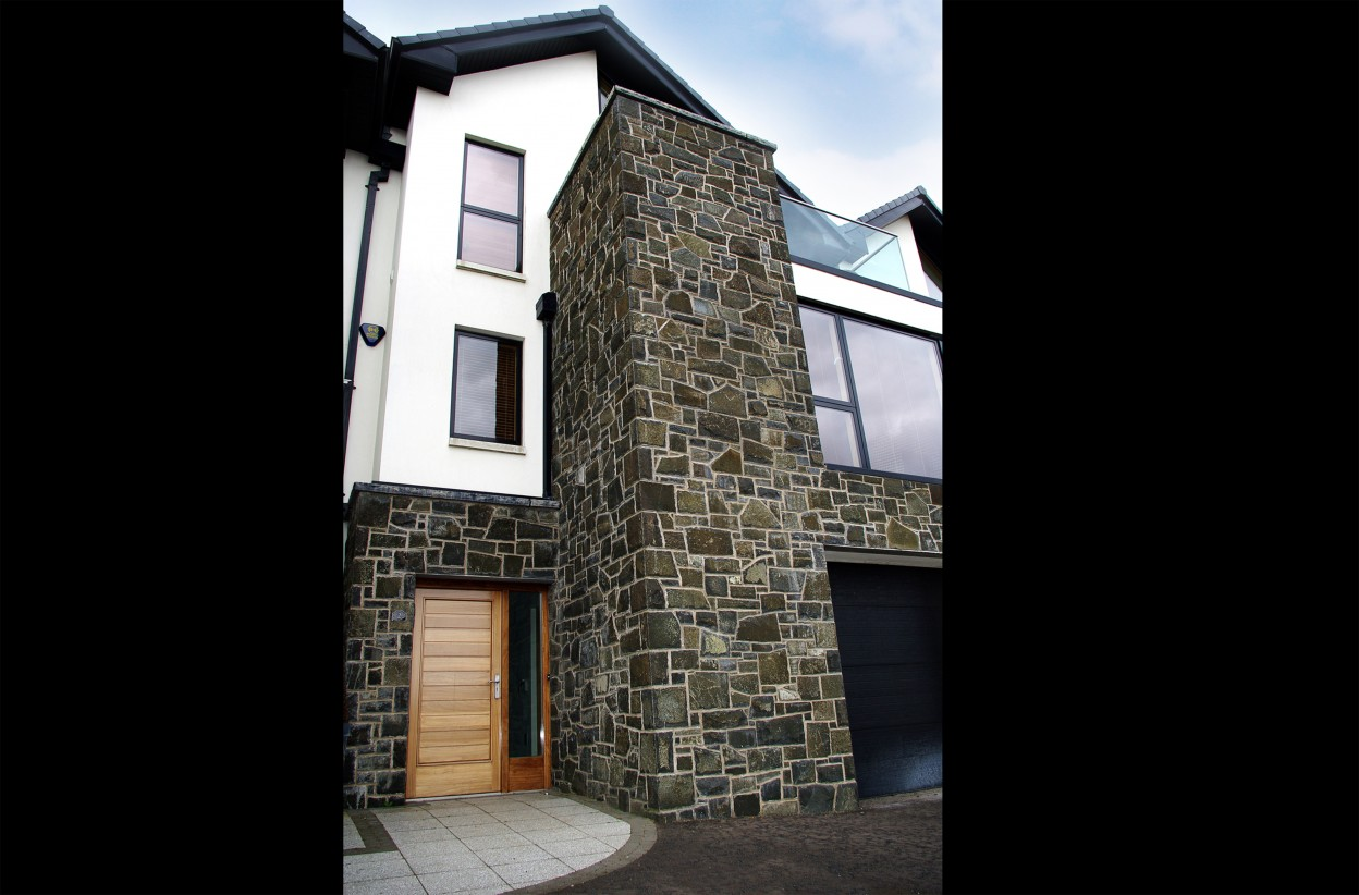 Natural faced basalt built across keystone lintels. Rock faced limestone wall copings