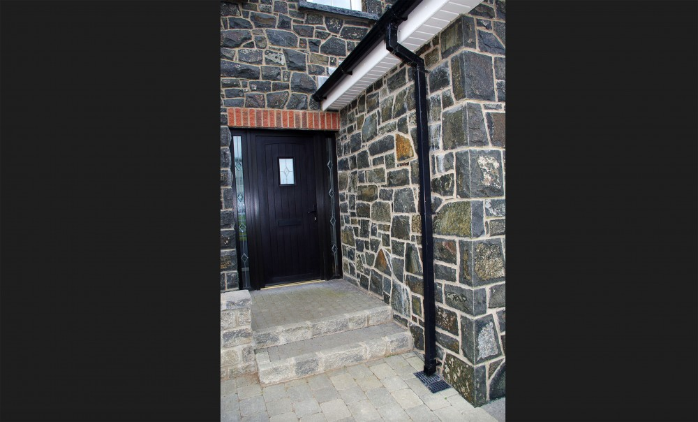 Natural face basalt stone. Brick soldiers above door. Hand pitched quoin edge