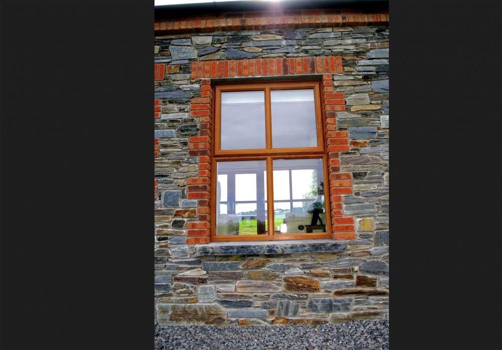 Donegal slate with red brick quoins. Red brick soldiers built on keystone lintel. Limestone hearths cut into window cills