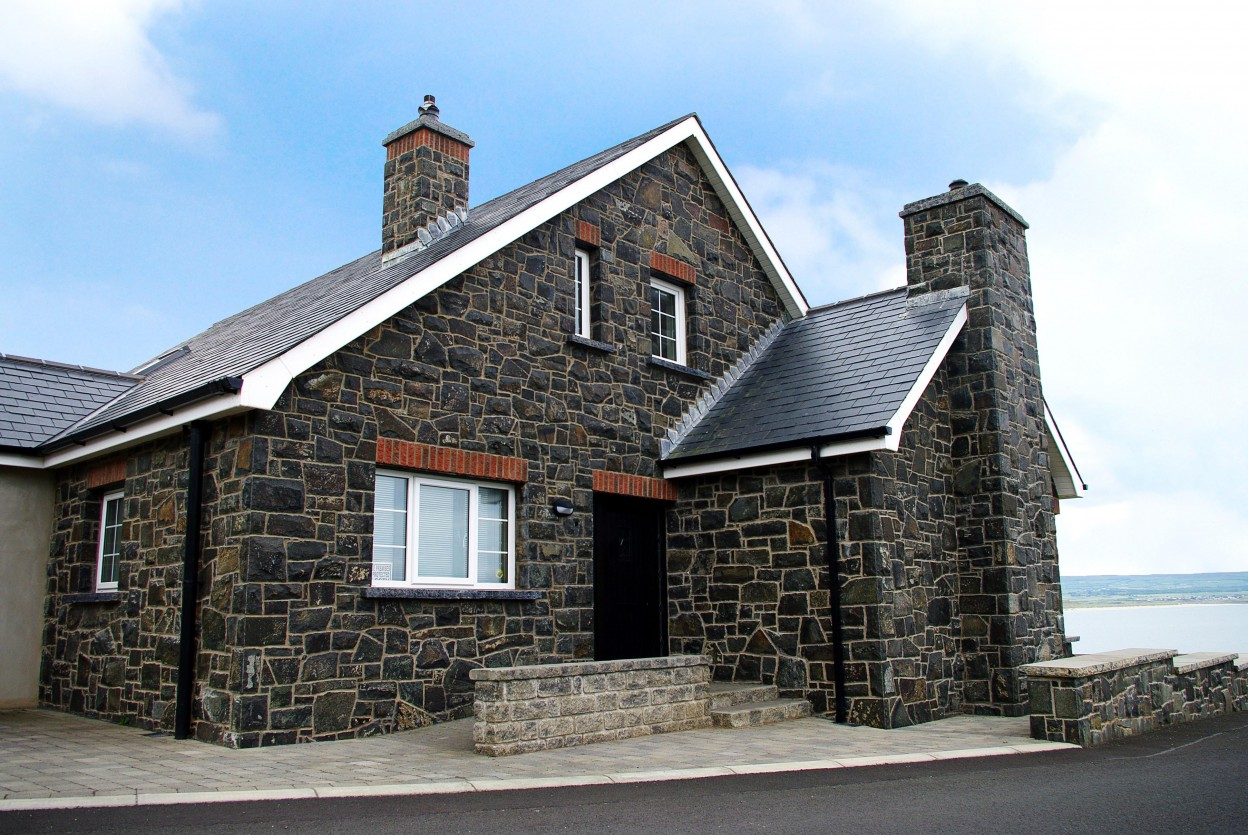 Natural face basalt with rock faced limestone window cills. Brick soldiers above window & doors. Rock faced limestone chimney coping. Hand pitched quoin edge