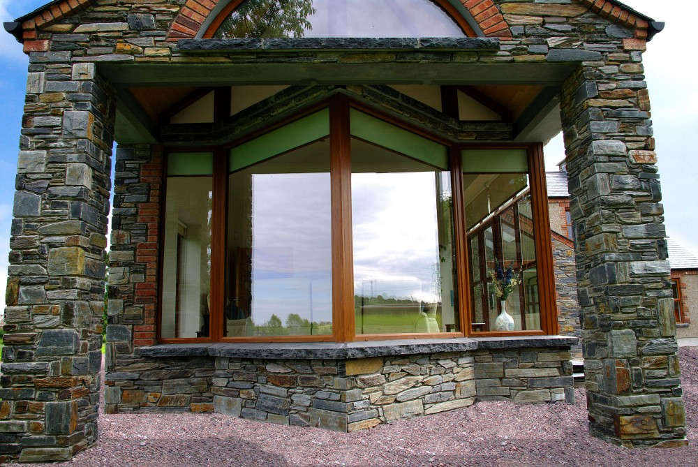 Donegal slate with 70% brown. Limestone hearths cut into window cills. Supporting pillars. Interesting V shaped window.