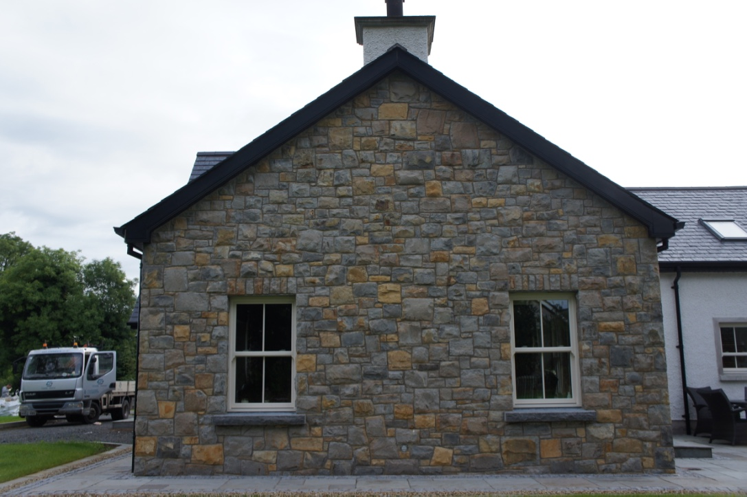 Blue Centre Sandstone mixed with Omagh Blue Stone. Rock faced limestone cills. Soldiers built on a keystone lintel