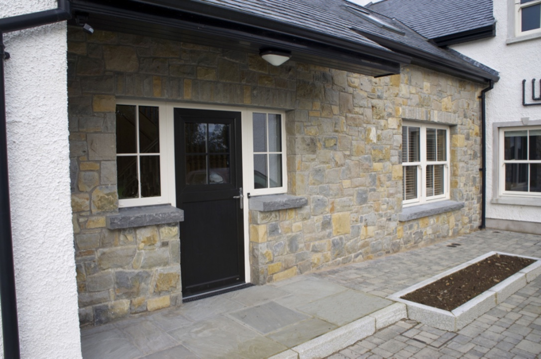Blue Centre Sandstone mixed with Omagh Blue Stone. Rock faced limestone cills