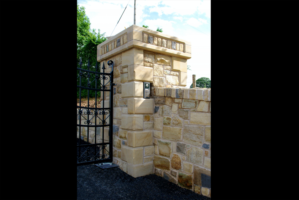 Chamfered sandstone quoins on pillar. Cut stone detail to pillar caps. Built in gate keypad