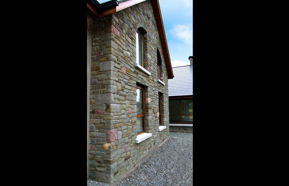Portlaoise Sandstone with Armagh Pink and Grey Limestone finished with grey granite window cills. Quoin detail to corner