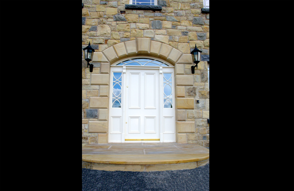 Cut & polished sandstone door arch with dominant keystone in centre. Donegal sandstone step with 10mm chamfer to tread and sandstone riser