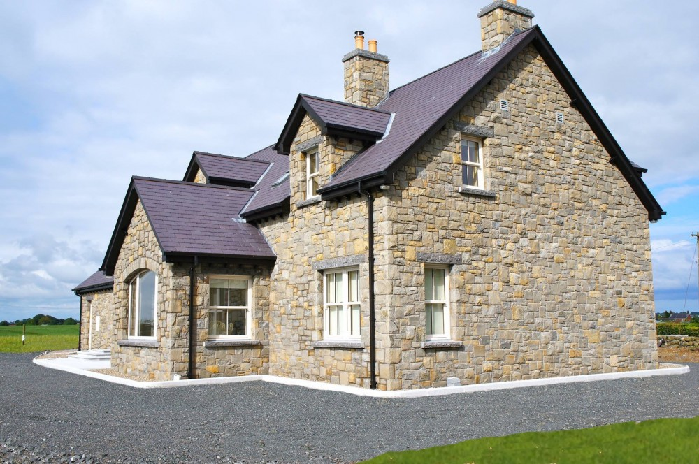 Blue centred sandstone, rock faced limestone window cills and lintels. Rock faced limestone double layered chimney copings. Self supporting window arch