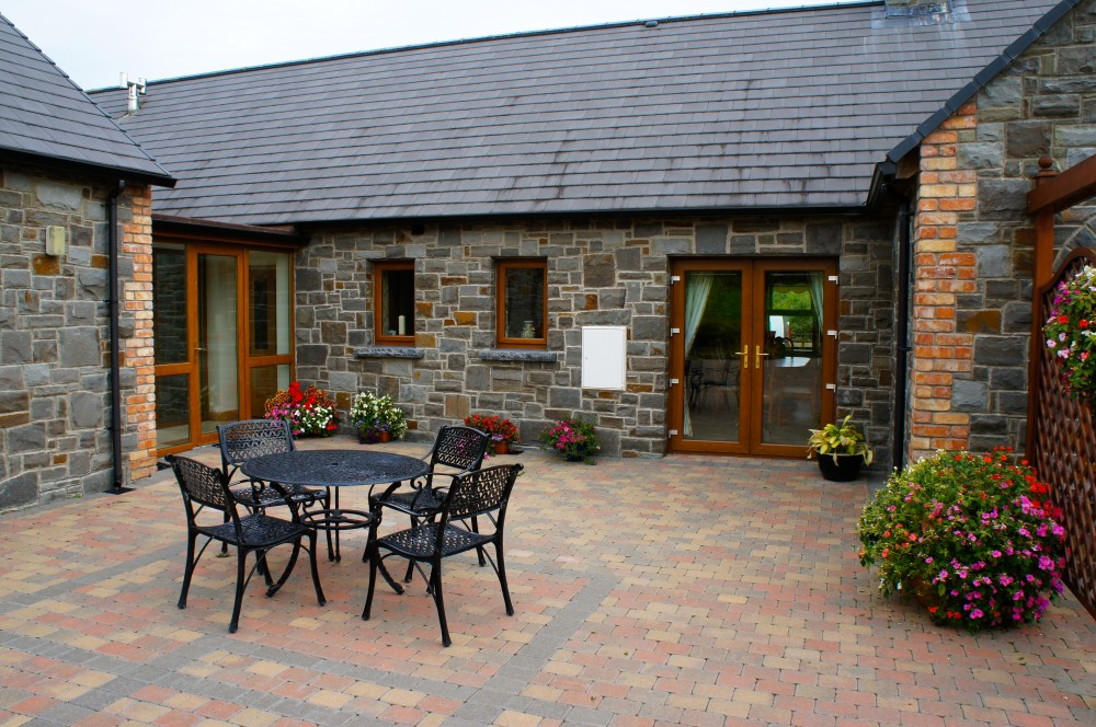 Clonmel Blue Sandstone with reclaimed red brick quoin detail. Limestone hearths cut as window cills