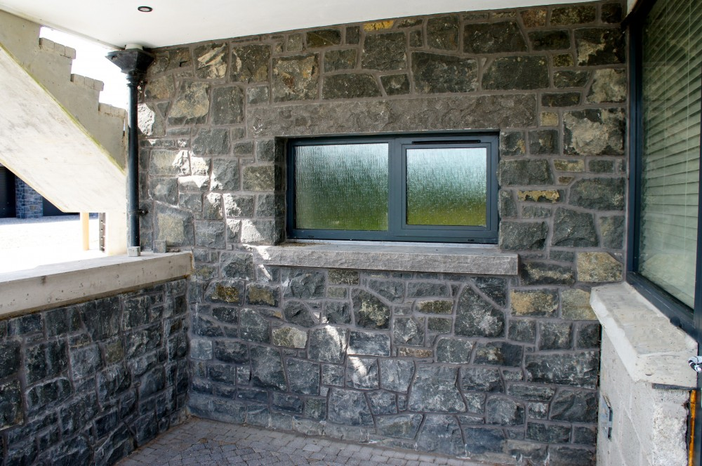 80% Split Face and 20% Natural Faced Basalt . Rock faced limestone window cills and lintels