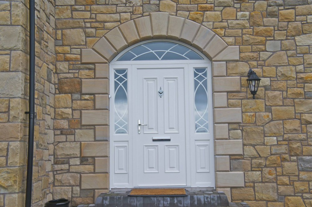 Sawn & polished sandstone arch and quoin detail to front door