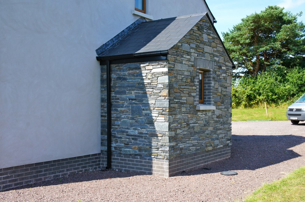 Donegal slate built with concrete window cills and grey brick quoin detail to windows