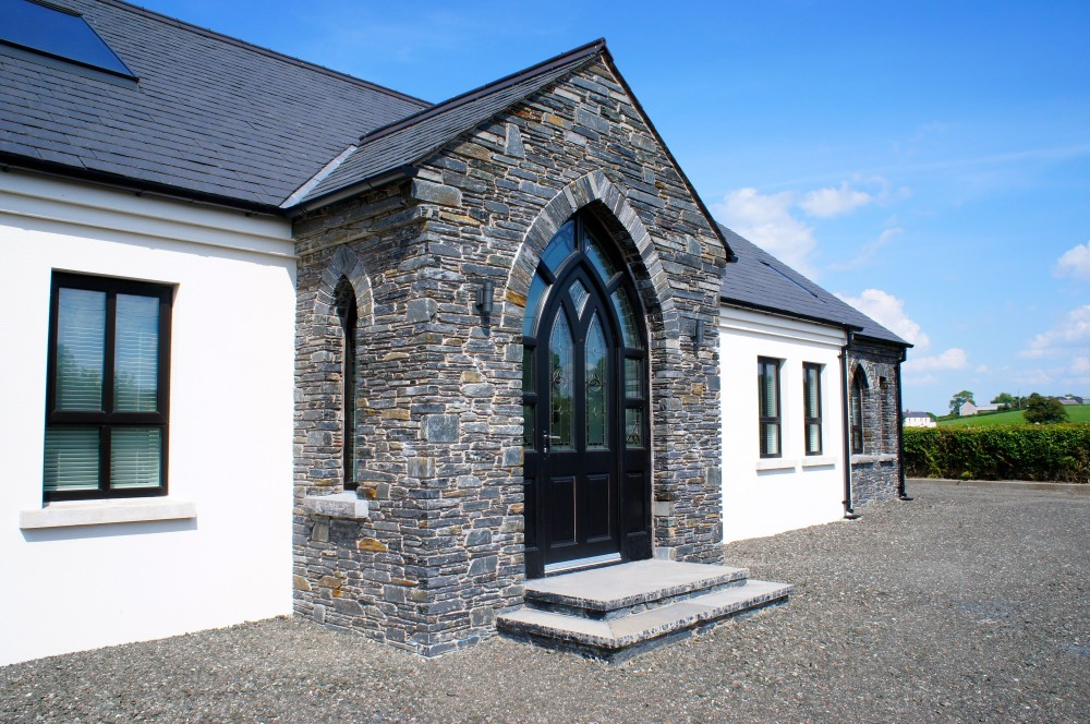 Donegal Slate porch with free standing gothic arch detail. Black limestone door steps