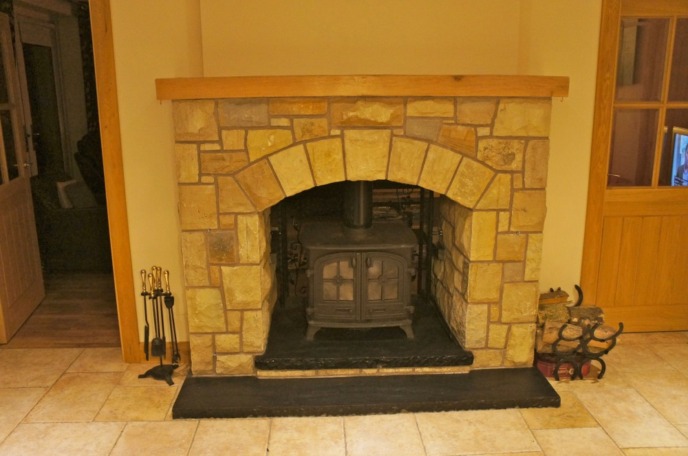 Double sided fireplace built with Donegal, Omagh and blue centred sandstone with black limestone split level hearth