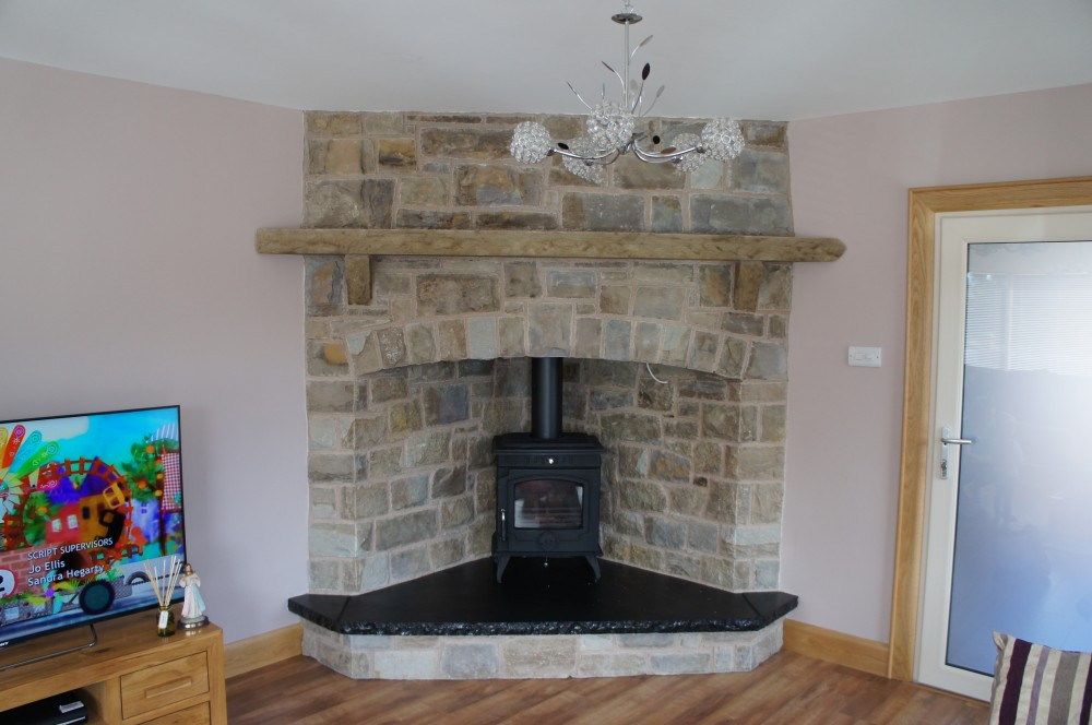 Tipperary brown and blue Sandstone corner fireplace with raised black limestone hearth