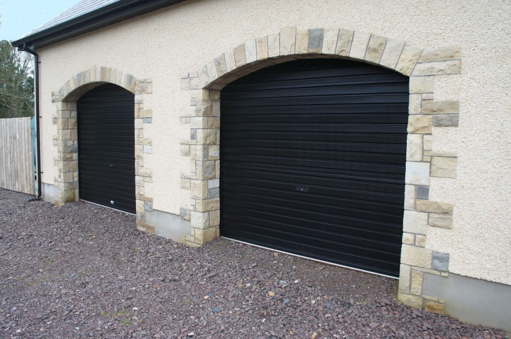 Quoin and arch detail built from building stone on garage openings