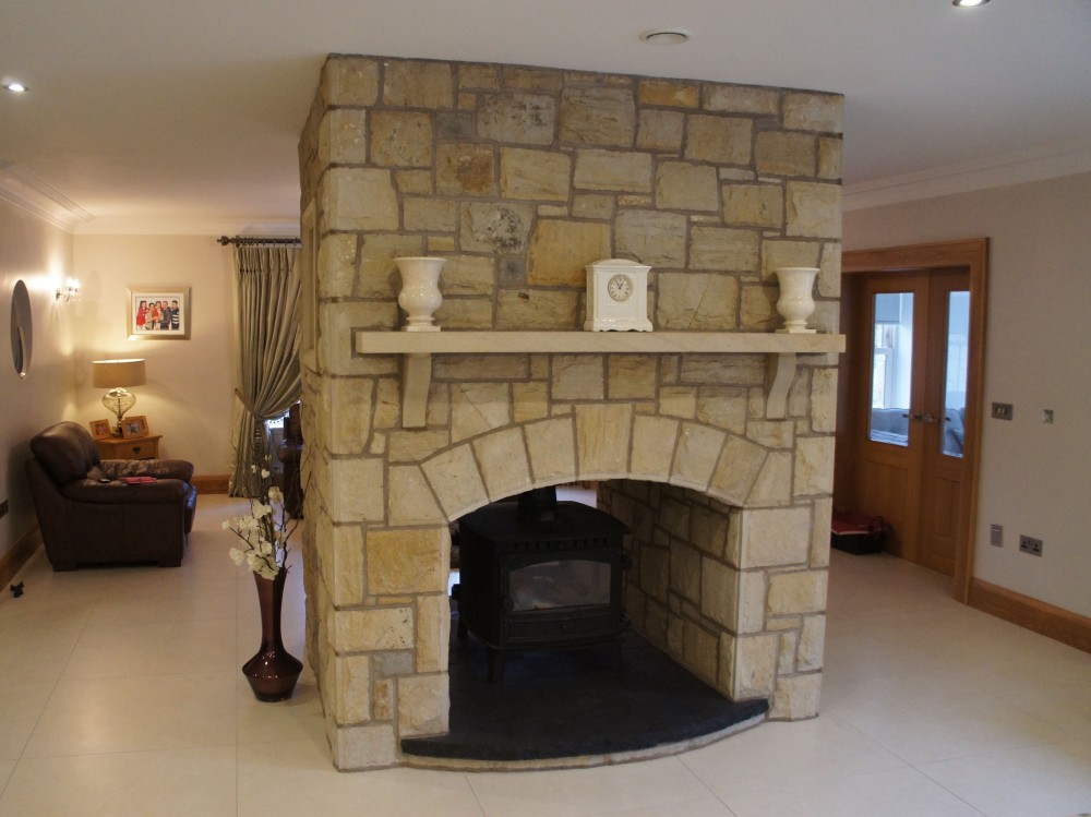 Rock faced sandstone mantle and corbels. Black limestone curved hearth
