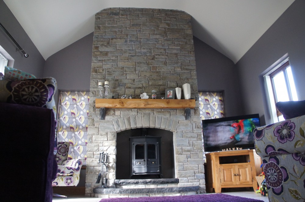 Portlaoise Sanstone fireplace with rock faced black limestone split level hearth