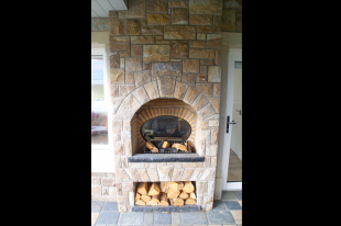 External Fireplace On Summer House Built From Tipperary Brown Stone. Free Standing Arch And Flat Arch And Fire Brick Insert. Log Holder Built In