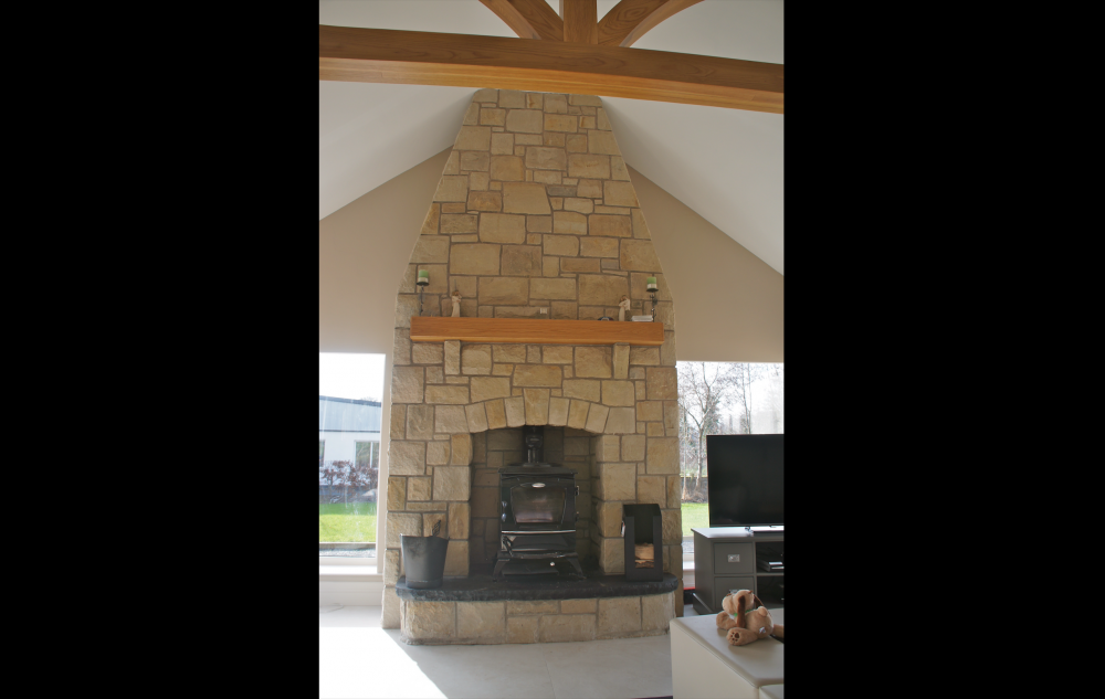 Reclaimed Leitrim sandstone with wooden mantle and rock faced sandstone corbels . Raised black limestone hearth