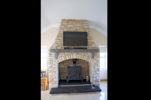 Donegal Quartzite With Kilkenny Limestone Mantle And Corbels. Rock Faced Limestone Split Level Hearth