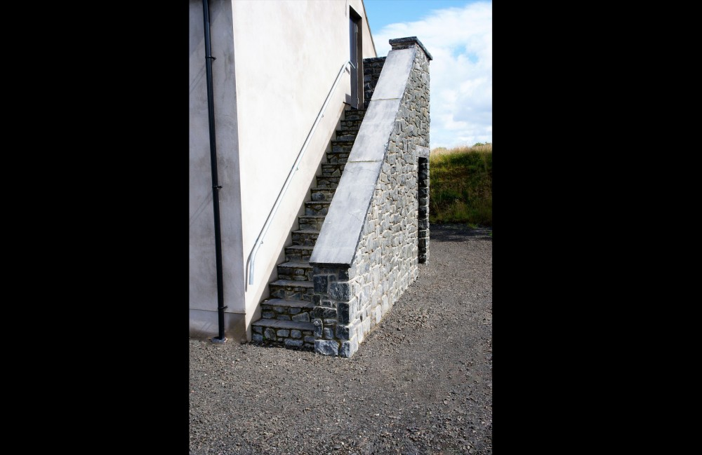 External stairs formed using tumbled basalt and black limestone treads