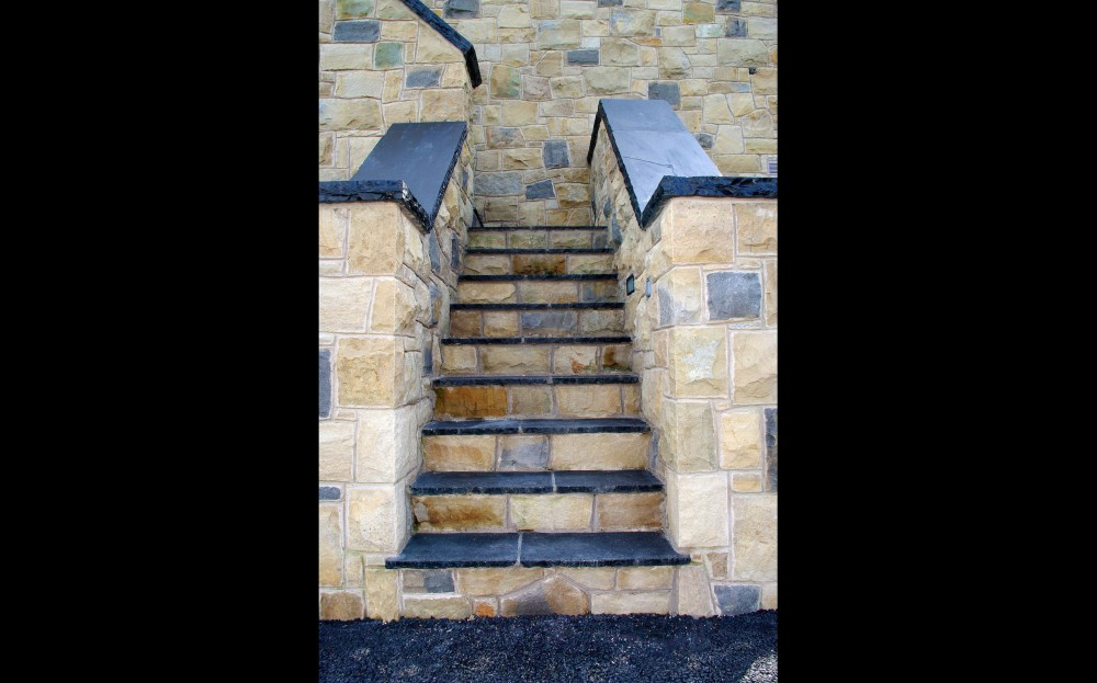 External steps with black limestone treads and sandstone risers. Black limestone wall copings