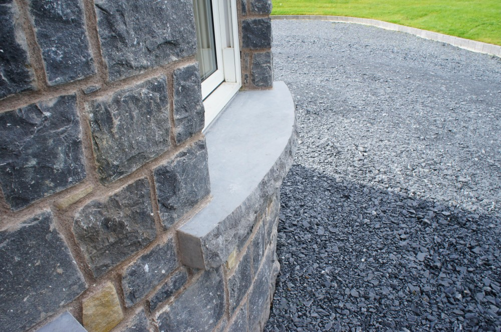 Curved rock faced limestone window cill