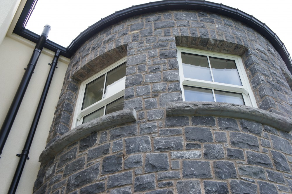Curved rock faced limestone window cills and curved self supporting flat arches