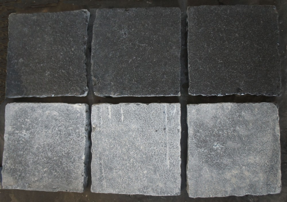 Tumbled black limestone cobbles. Wet on top and dry on bottom