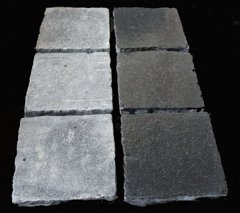 Tumbled black limestone cobbles. Dry on left and wet on high