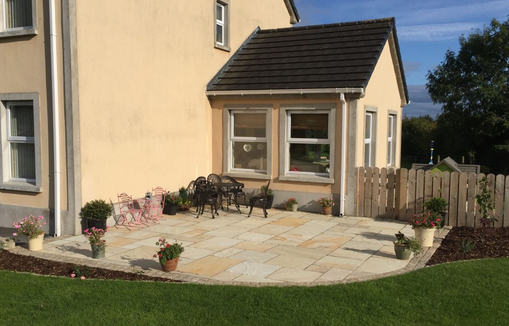 Tumbled tinted mint paving with gold granite cobble border