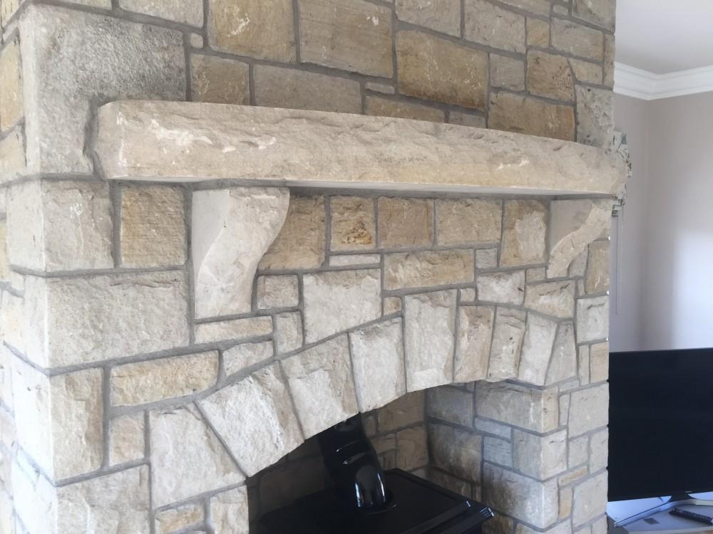 Curved rock face sandstone mantlepiece with rock faced sandstone corbels
