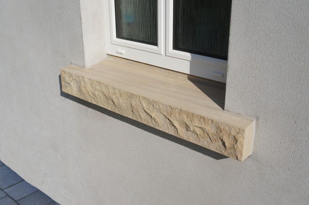 Rock faced sandstone window cills in rendered areas
