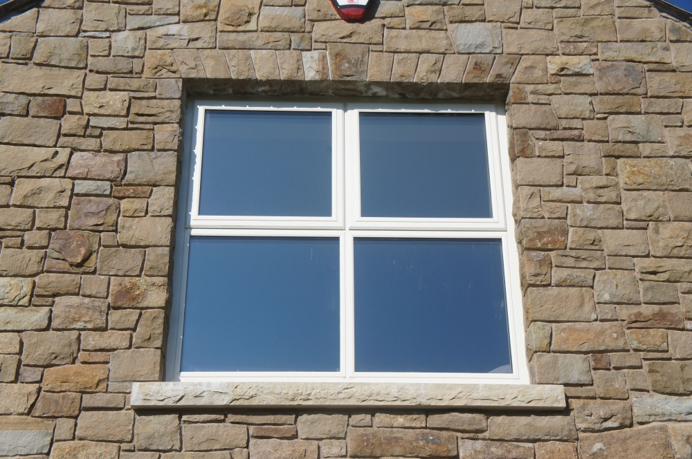 Free standing flat arch and Rock faced sandstone window cill