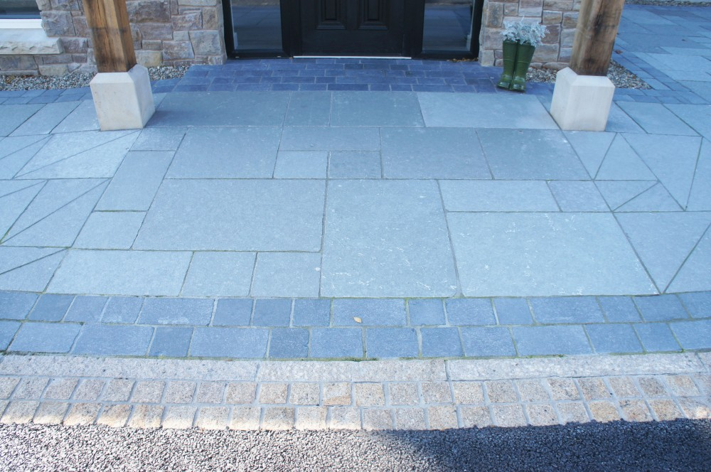 Grey limestone paving with tumbled black limestone border and gold granite split cobbles