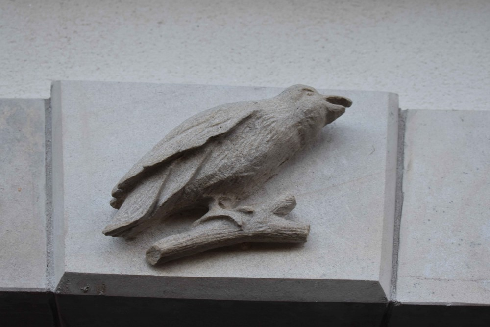 Crow hand carved into keystone on garage door surround